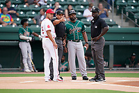 Umpires Ray Valero, left, and James Jean meet with manager Iggy Suarez (2) of the Greenville Drive and Kieran Mattison (24) of the Greensboro Grasshoppers on Tuesday, July 20, 2021, at Fluor Field at the West End in Greenville, South Carolina. (Tom Priddy/Four Seam Images)