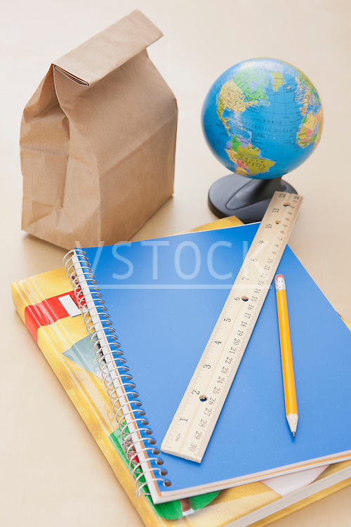 Studio shot of notebook, lunch bag and globe