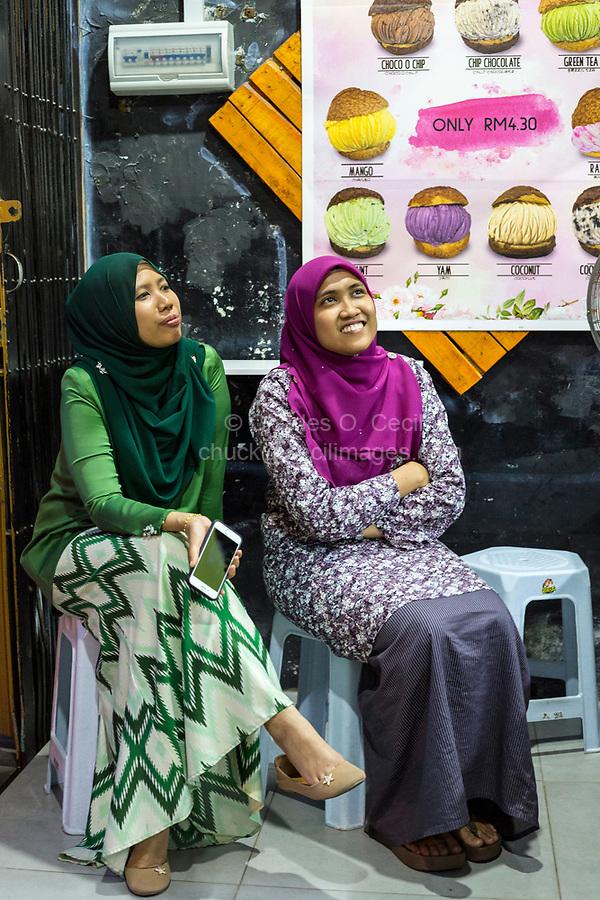 Young Malaysian Women in Ice Cream Shop Wearing Typical Modern Malaysian Dress, Ipoh, Malaysia.
