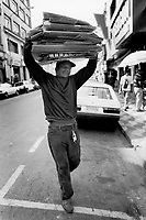 """Brazil. Sao Paulo state. Sao Paulo. Alessandro is 38 years old. He is a black poor man who lives in the street. He carries a pile of carboards on his head. The """"catadores"""" are men who collect paper, plastics, metals, bottles ... in order to sell these items as recycled materials and make a living. Waste collector. © 1994 Didier Ruef .."""