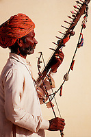 A portrat of an Indian musician in profile holding his string instrument. India.