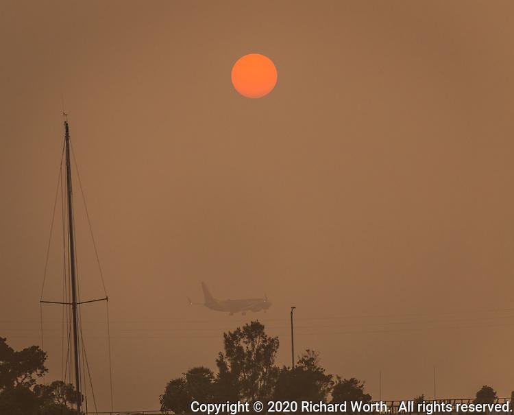 A passenger jet approaches Oakland International Airport under a smokey orange sun on September 14, 2020.