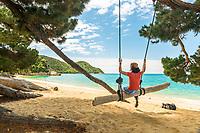 Young woman enjoying swing on Anatakapau Bay on Abel Tasman Coast Track, Abel Tasman National Park, Nelson Region, South Island, New Zealand, NZ