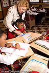 K-8 Parochial School Bronx New York Grade 3 mathematics lesson on measurement using rulers female teacher looking over student's work vertical