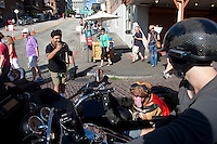Crowds at Pike Place Market in Seattle, Washington flock to see Lucy, a pit bull mix, riding in a sidecar next to her mom, Brande Schweitzer, who drives a Harley-Davidson.