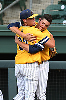 Starting pitcher Jake Lewis (32) of the UNC Greensboro Spartans, left, is embraced by Bryce Hensley after Lewis came out of the Southern Conference Championship final game against the Furman Paladins in the sixth inning on Sunday, May 28, 2017, at Fluor Field at the West End in Greenville, South Carolina. UNCG won, 13-1, and Lewis got the win. (Tom Priddy/Four Seam Images)