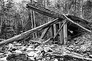 Side view of a collapsed timber bridge at the Sokokis Brook crossing along of the abandoned Boston and Maine Railroad's Mt Washington Branch (between Fabyans and the base of the Cog) in the White Mountains, New Hampshire. The Boston, Concord & Montreal Railroad completed the roughly six and a half mile long extension from Fabyans to the base of the Cog Railway in 1876.