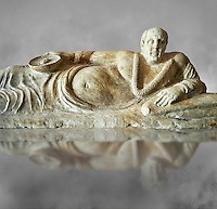 Close up of an Etruscan Hellenistic style cinerary, funreary, urn cover with a man,  National Archaeological Museum Florence, Italy , grey art background