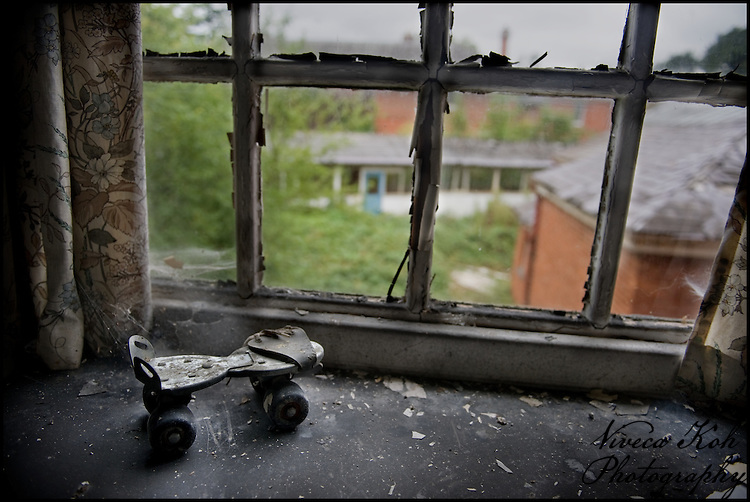 Solitary roller skate on the window sill of an abandoned asylum.