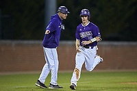 Daniel Walsh (19) of the Western Carolina Catamounts slaps hands with \third base coach Bobby Moranda as he jogs towards home plate during the game against the St. John's Red Storm at Childress Field on March 12, 2021 in Cullowhee, North Carolina. (Brian Westerholt/Four Seam Images)