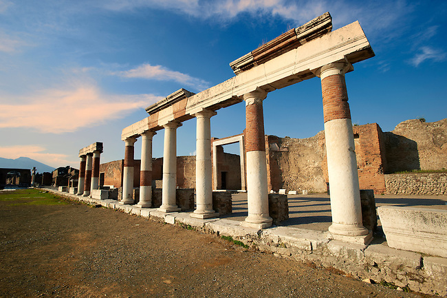 """The Roman Columns of The Building of Eumachia, Pompeii. The inscription on lintel above the columns is to Concordia Augusta, wife of Emperor Augustus, from the priestess Eumachia the patron of the """"fullones"""", an artisan association of dyers. The building was a prototype of medieval hostels were travelling merchant rented accommodation."""