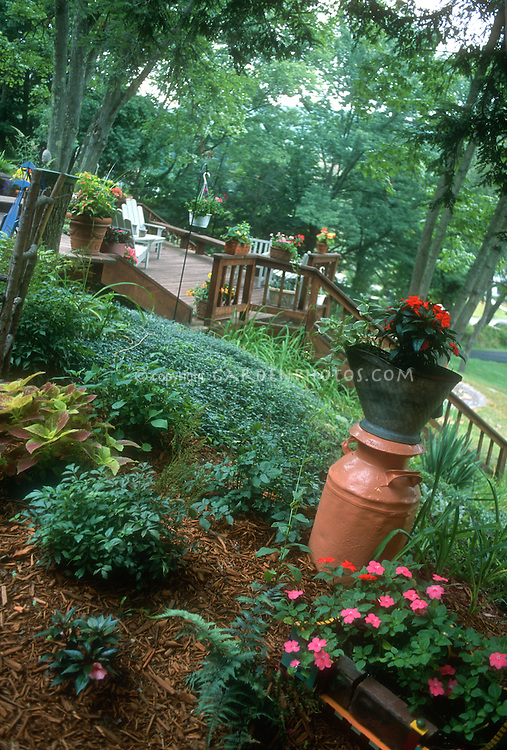 Hillside shaded backyard with deck, container plants, groundcover, coleus, impatiens, flea market finds of old coal scuttle and urn being used in the garden, upcyled ornaments, sloped gardening