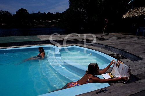 Anavilhanas, Amazon, Brazil. Female Spanish tourists relaxing in a pool set in the rainforest in a jungle lodge.