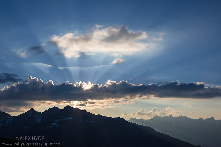Crepuscular rays at sunset over the mountain landscape of the Samnaungruppe, a subgroup of the Central Alps. Nordtirol, Austrian Alps. July.