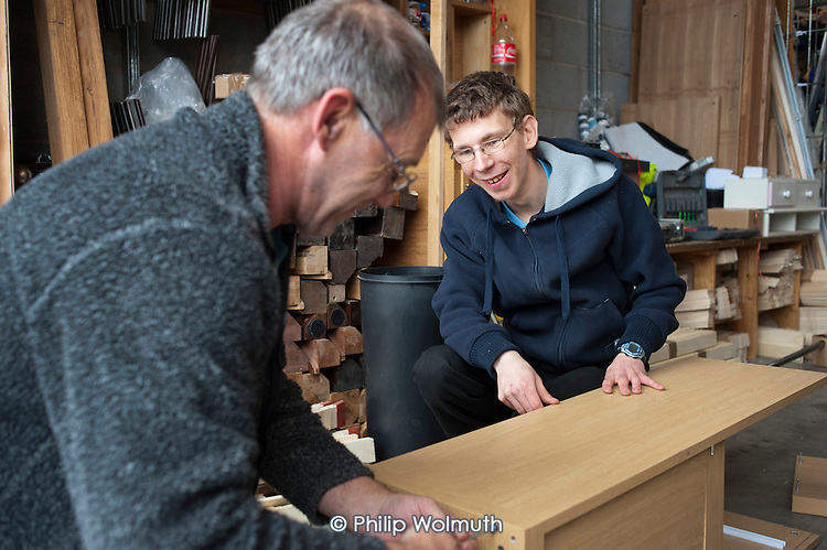 Ex-miner working on a rolling 3 month, Minimum Wage contract, with placement Matthew, who has cerebral palsy, at Doncaster Refurnish, a recycling social enterprise, South Yorkshire. The business takes damaged furniture from national retailers and works with trainees, offenders, welfare-to-work placements and employees on contract to supply its network of low-cost shops.
