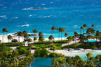 Aerial view of a luxury hotel pool, palm trees, and white sand beach, on the turquoise Atlantic Ocean water, on Paradise island, Bahamas
