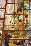 Deutschland, Bayern, Niederbayern, Naturpark Bayerischer Wald, Viechtach-Rauhbuehl: Die Glaeserne Scheune - Lebenswerk des Glasmalers Rudolf Schmid senior - er malte Geschichten aus dem Bayerischen Wald auf und hinter Glas, hier z.B. die symbolische Darstellung des Muehlhiasl - dem Waldprophet. Der Kuenstler erklaert einer Besucherin die Bedeutung der einzelnen Bilder | Germany, Bavaria, Lower-Bavaria, Nature Park Bavarian Forest, Viechtach-Rauhbuehl: The Glassy Barn - life's work of glass painter Rudolf Schmid senior - painting legends of the Bavarian Forest. The artist explaining his work to a visitor