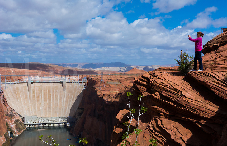 Page Arizona Glen Canyon Dam on Colorado River woman tourist taking Iphone pictures scenics with rocks and clouds for tourists West USA from above   7