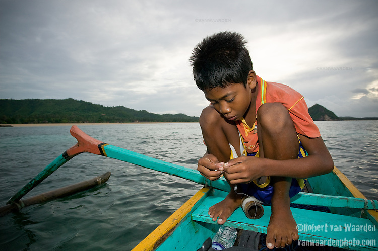 Sunardi, the son of Syria, prepares a line to catch fish. Syria fishes everyday, quite often accompanied by his son,.Typically they will catch 30 - 50 small fish per outing. These will be sold at the market and they live on approximately 7 dollars US a month.