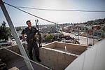 Irak - Kirkuk. Ein schwer bewaffneter Soldat steht auf einem Hausdach und bewacht die Region.<br /> <br /> Engl.: Asia, Iraq, Kirkuk, armed soldier, roof, June 2014