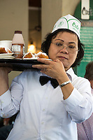 French Quarter, New Orleans, Louisiana.  Waitress Delivering Beignets and Drinks at the Cafe du Monde, famous for its coffee and beignets.