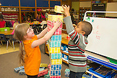 MR / Schenectady, NY. Zoller Elementary School (urban public school). Kindergarten inclusion classroom. Students build tall structure together using large cardboard blocks at free playtime. Girl left: 6; boy right: 5, African American. MR: Man6, Ste14. ID: AM-gKw. © Ellen B. Senisi.