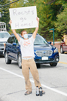 """A man holds a sign reading """"Racists go home!"""" as Donald Trump, Jr., son of president Donald Trump and a rising Republican political star, leaves after speaking at an outdoor campaign rally at The Lobster Trap in North Conway, New Hampshire, on Thu., Sept. 24, 2020."""