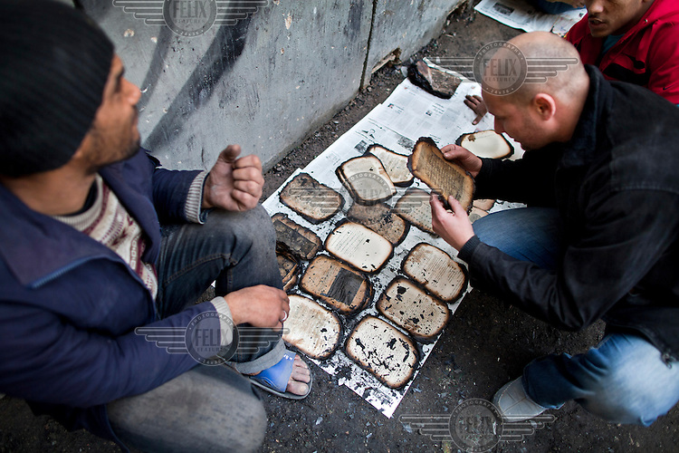 Volunteers remove sorched book remains from the Institute of Egypt building in Cairo, Egypt. The building contained some 192,000 books, journals and writings, some dating back to the 16th century. It caught fire during clashes between protesters and the Egyptian military...