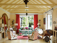 The sitting room, with its exposed ceiling rafters is light and airy. Magenta taffeta curtains and bold chintz upholstery bring accents of pink colour to the room. Two sets of French doors open out onto the garden.