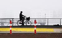 Nederland  Amsterdam - 2 jan 2021.  Mist. Fietsen langs het IJ.  Foto is gespiegeld mbv Photoshop.    Foto : ANP/ HH / Berlinda van Dam