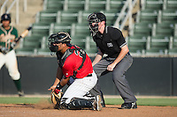 Kannapolis Intimidators catcher Daniel Gonzalez (23) blocks a pitch in the dirt as home plate umpire Tyler Jones looks on during the game against the Greensboro Grasshoppers at Intimidators Stadium on July 17, 2016 in Greensboro, North Carolina.  The Grasshoppers defeated the Intimidators 5-4 in game two of a double-header.  (Brian Westerholt/Four Seam Images)