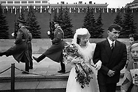 Russia. Moscow. A newly married couple stands on the Red Square. The bride wears a white wedding dress, a hat and a veil. She holds a bouquet of flowers and the groom's arm. In their back, a group of soldiers, all presidential guards, march to shift change for watch duty at Lenin mausoleum. The Red Square is a city square and is often considered the central square of Moscow. View on the Kremlin and its protective walls. Moscow is the capital and largest city of Russia. 14.09.1993 © 1993 Didier Ruef