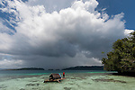 West Papuan fisherman in his outrigger house boat leaving the shallow island