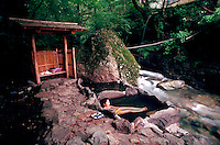 Shima onsen - a bather enjoys the tranquil setting of a Japanese outdoor hot spring bath nestled in a rock grotto. MR. Shima prefecture, Japan.