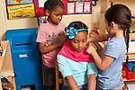 Education Preschool Headstart pretend play girls giving another girl a hair cut or new hair style
