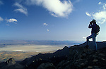 Man with binoculars at summit of Steens Mountain looking at Alvord Desert; southeast Oregon.