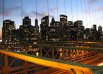 View of New York City skyline through Brooklyn Bridge cables at sunset.