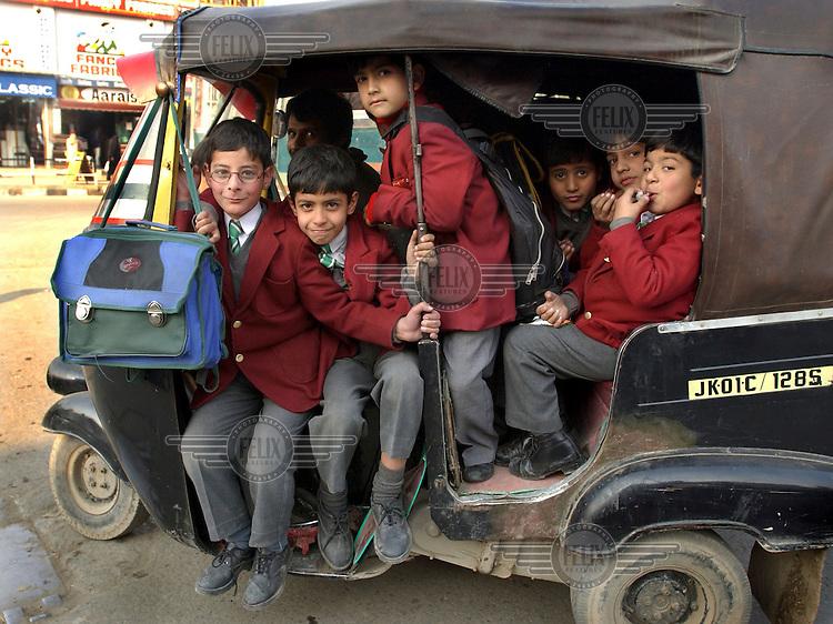 Children cram into a rickshaw on their way back from school.