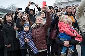 Tourists use smartphone cameras at Buckingham Palace, London.