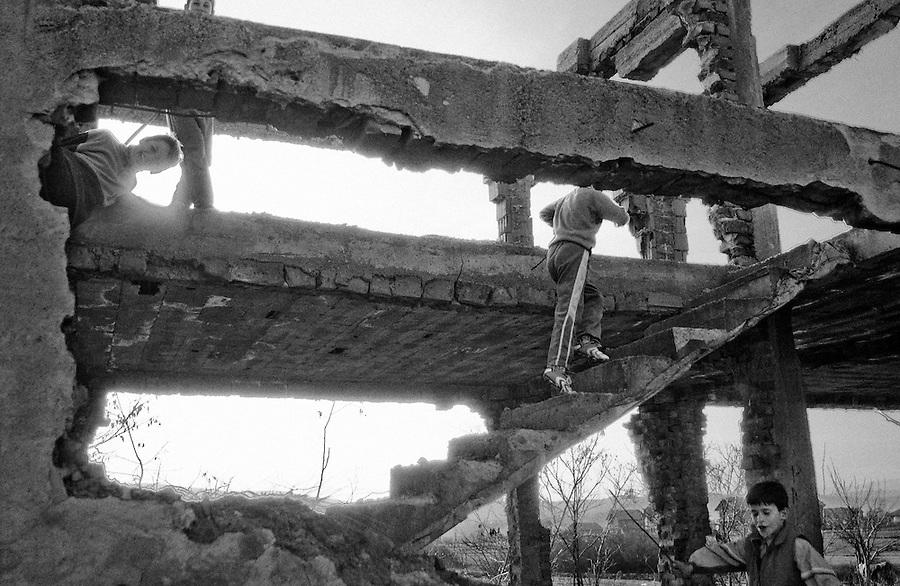 Ethnic Albanian children play amongst destroyed Serbian house in Kosovo.