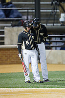 Wake Forest Demon Deacons head coach Tom Walter (16) gives instructions to Joey Rodriguez (8) during the game against the Delaware Blue Hens at Wake Forest Baseball Park on February 13, 2015 in Winston-Salem, North Carolina.  The Demon Deacons defeated the Blue Hens 3-2.  (Brian Westerholt/Four Seam Images)