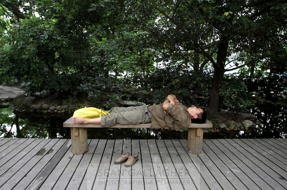 """A man sleeps in the """"Living Water Garden"""" in Chengdu, Sichuan Province. The garden is a park aimed at highlighting the importance of the relationship between man and water. 2010"""