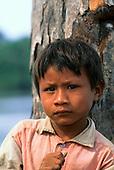 Mato Grosso, Brazil. Young Rikbaktsa (Canoeiro) Indian boy next to a tree.