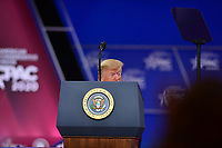 National Harbor, MD - February 29, 2020: U.S. President Donald J. Trump crouches behind the podium as he tells a joke before attendees at the Conservative Political Action Conference (CPAC) 2020 hosted by the American Conservative Union at the Gaylord National Resort at National Harbor, MD, February 29, 2020.  (Photo by Don Baxter/Media Images International)