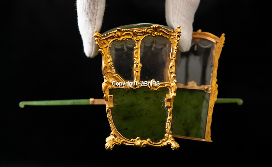 BNPS.co.uk (01202 558833)<br /> Pic: PhilYeomans/BNPS<br /> <br /> Miniature marvel...<br /> <br /> In from the cold - £500,000 Romanov treasure is hot property at Cotswold auction.<br /> <br /> An exquisite Faberge antique believed to have been made for the Russian Royal family over 100 years ago sold yesterday for a whopping £500,000...over 5 times it's estimate.<br /> <br /> The model of a sedan chair by the iconic Russian jewellers was one of the state treasures seized and sold off by the communist regime following the Russian Revolution.<br /> <br /> It was first sold at high-end Anglo-Russia antique dealers Wartski in London in 1929, where it was bought by a K.W Woollcombe-Boyce for only £75.<br /> <br /> The ornate item, crafted from Jadeite, gold, rock crystal and mother of pearl, has remained in the family ever since and is now being sold by a direct descendant of Mr Woollcombe-Boyce.<br /> <br /> Experts from the Cotswold Auction Company gave the small Russian antique a pre-sale estimate of only £100,000, but always anticipated it could go for much more than that.