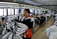 A worker ferries half-finished clothing pieces between sewing stations at the Shengyuan Clothing Factory in Suzhou, Jiangsu Province, China. The factory employs a total of 250 workers that works year-round to fill clothing orders from Adidas and has expanded its operations to a more rural area of the province to meet the demand and cut down labor cost..16-OCT-04