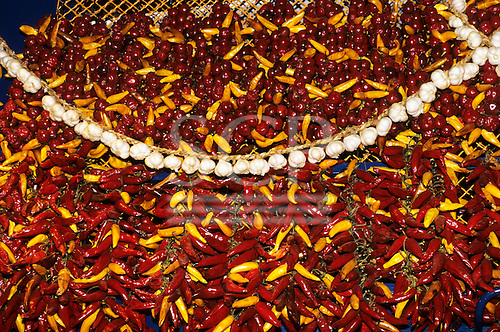 Budapest, Hungary; yellow peppers, paprika and garlic displayed on a market stall.
