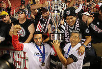 Dwayne De Rosario (l) and owner Will Chang (r) of D.C. United celebrate their win with the trophy and fans over Real Salt Lake at the U.S. Open Cup Final on October 1, 2013 at Rio Tinto Stadium in Sandy, Utah. DC United beat Real Salt Lake 1-0 to win the championship.