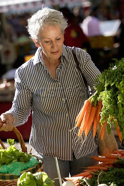 Older female person choosing vegetables