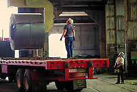 Unloading rolled steel from truck at steel fabrication plant. Birmingham Alabama, Copperweld.